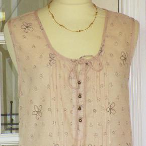 Feminin kjole i 100 % cotton. Kjolen har flot bordüre-bort forneden. Bundfarven er gl. rosa. Oprindelig købspris: 600 kr.  Brystvidde: 52 cm x 2 Hoftevidde: max 65 cm x 2 Længde: 90 cm  Ingen byt, og prisen er fast