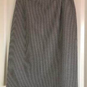 Sort/hvid mønstret nederdel, med lederkant i toppen. Har slids bagpå. Størrelse M (længde: 65cm)