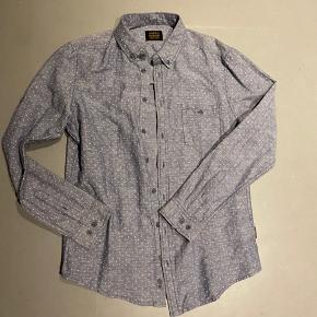 Rigtig fin hverdagsskjorte i en flot grå farve med hvide brodderede prikker. Aldrig brugt, men prismærke er taget af.