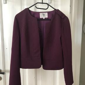 Fin blazer jakke i burgundy (mørkelilla/bordeaux).  Aftagelig peplum kant (med trykknapper) samt lille hæfte til at kunne lukke jakken.  Farven er mest retvisende på billede 1.   Kan sendes eller afhentes i Rødovre.