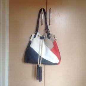 Fin håndtaske/skuldertaske. Måler ca 48 x 30 cm med hanke på 52 cm. Indvendig er der et stort rum, 2 mindre rum med lynlås og to små rum til småting. Bagpå tasken er der også et lille rum med lynlås og tasken kan lukkes både med lynlås og snor.
