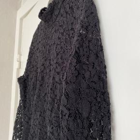 Elegant kjole i med sort blonde.  To lags i den nedre del samt foran midtpå. Ved ærmerne, det øverste af ryggen samt de nederste par centimeter er der kun et lag blonde og man kan se gennem. Den lukkes bagpå med lynlås og knapper.