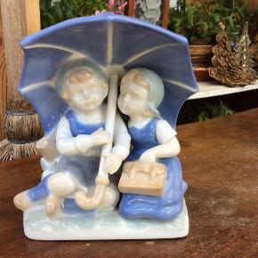 Børn, sødeste dreng og pige under paraply, ukendt porcelæn, måler 10 cm lang og 13 høj. Drengen til venstre har en lille prik på kinden, det er noget der er i porcelænet. mp 145. Se mine andre annoncer.