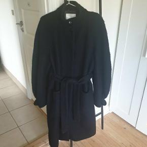 Stine Goya Celeste frakke i str. M. Materialesammensætningen er 67% uld og 33% polyester. Har løs pasform med bindebånd i taljen, to lommer og lukkes med tre knapper ved halsen og trykknapper ned langs kroppen. Det sidste billede er for at vise frakkens pasform.  Nypris 4000 kr.