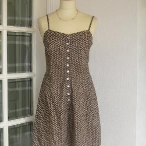 """Mrk.: """"Hennes""""  100 % NY: Sød bukse-kjole i 100 % cotton. Ideel til en varm sommerdag. Brystvidden kan justeres med den sløjfe der bindes bag på ryggen. Farve: Brun m. hvide blomster  Brystvidde: 48 cm x 2 (kan justeres) Livvidde: 41 cm x 2 Længde 91 cm.  Ingen byt og prisen er fast"""