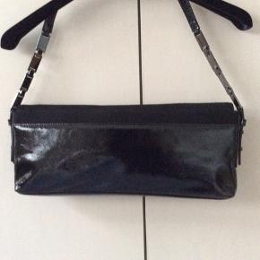 Flot sort lak og uld taske med indvendig lynlåsrum og udvendig rum bag.Der er magnetlås. Højde 15 cm Bredde 35 cm Dybde 3 1/2 cm Rem kan gøres længere.