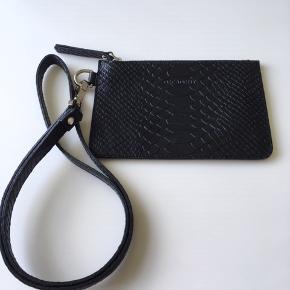 Keyhanger/nøglesnor med vedhæftet pung. Pungen måler 10,5 x 15 cm.  Er i sort præget skind