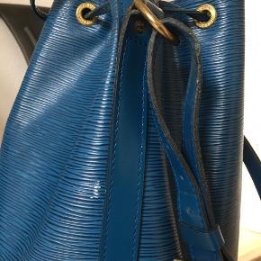 Mega lækker Louis Vuitton BLUE EPI NOE Lavet i kraftigt  Epi læder  Denne taske er en design klassiker, som kan bruge til alle lejligheder fra skole/arbejde til fest! designet til at bære champagneflasker så den kan holde til en del ;)  Den kan bæres Crossbody, men kommer selfølgelig an på din kropsbygning vil jeg sige.   Date code: AR 1903  Measurements: 28 x 36 cm Shoulder drop: 28 cm  Der hører ingenting med, hverken, kvit, dustbag eller andet!  Selfølgelig 100% ægte og jeg står også inde for den er ægte.   Sender gerne billeder, men skriv hvad du gerne vil se, tak.