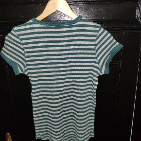 Virkelig blød stribet bomuldst-shirt i rib med søde trykknapper foran. Striberne er grå og grangrønne og svarer til billede 2 og 3.