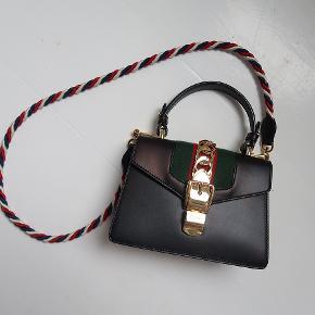 Gucci 'Sylvie' taske sælges. Tasken er sort med guld hardware. Den er brugt nænsomt og i rigtig fin stand, men har enkelte misfarvninger, som jeg faktisk først bemærkede, da jeg tog billederne af den. De bemærkes stort set ikke, men jeg forsøgte at tage billederne i et lys, hvor de ses.   Tasken er fra Net-a-porter og kostede 1.690 britiske pund, hvilket svarer til 14.500 kr.  Mål: 14 x 8 x 20 cm.