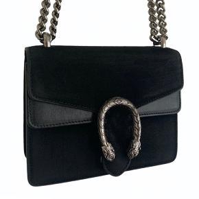 Gucci Dionysus Mini Crossbody Bag i sort ruskind. Kvittering, dustbag og Gucci-pose/æske medfølger. Nypris 10.400 kr. Købt i Milano.  Der er noget slidtage på skindet, primært på bagsiden, men fremstår stadig rigtig fin. Tasken kan både bæres over skulderen og crossbody. Flere billeder kan fremsendes, og tasken beses og afhentes i København😊