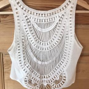 Hvid crop top med åben/synlig ryg i crepe stof. Fra H&Ms Coachella kollektion. Boho/festival/sommer top med blonde/broderet ryg.  Aldrig brugt, kun vasket en enkelt gang.  Kan give mængderabat ved køb af mere end én ting.