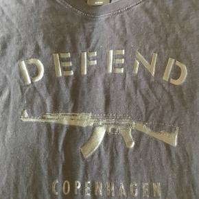Supercool t-shirt fra Defend Copenhagen i pæn stand. Den er sort med sort tryk. Det ene billede snyder lidt, så den ser grå ud. Trykket er, som det skal være:-). Str. L, men passer nok mest en M (brugt af dreng på 180 cm.)