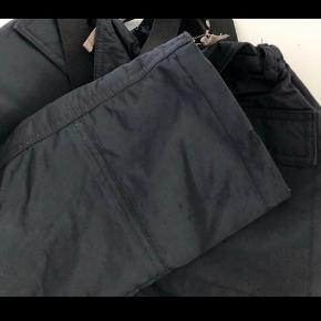 Lækre sorte skibukser. Fin stand -har kun lidt små overflade ridser i stoffet nederst på buksebenet  og en meget lille flænge nederst i kanten der er syet -se billeder -stoffet er ikke misfarvet, det er lyset der reflekterer. Kan reguleres i livet og selerne kan lynes af. Str 7 Kommer fra røg og dyre frit hjem