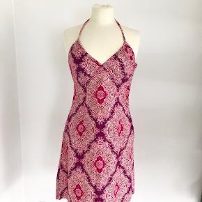 Sød sommerkjole fra H&M i pink, råhvid og lilla.  Der er bindebånd i nakken, smock-elastik på ryggen og lynlås i venstre side.  Længde fra nakken er ca. 104 cm (afhængig af, hvordan bindebåndet bindes).  Brystmålet er 90 cm, og taljen måler 86 cm.  Fremstillet af bomuld.  Bærer ikke præg af brug.