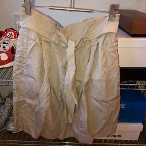 Fin nederdel med bindebånd, stopper midt på låret, trænger til dampning