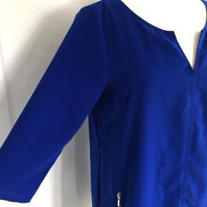 Smart kjole fra H&M i den flotteste blå farve.  Ærmerne er 3/4 lange. Der et to lommer foran på kjolen, og de lukkes med lynlås.  Længde fra skulder er 91 cm, og brystmål og taljemål er 108 cm.  Fremstillet af polyester.  Bærer ikke præg af brug.