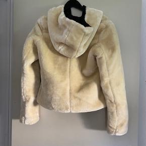 """Fineste """"isbjørn"""" agtig jakke, købt hos just a Girl for en del år siden. Både pels og læder er fake. Har en lang tråd foran nederst ved lynlås og har fået noget brun plet bagved. Overskudstråde haves"""
