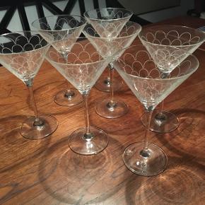 Syv fine cocktailglas med fint dekorativt mønster på glasset. 11 cm i diameter og 18 cm høje. Kan også bruges til en let dessertanretning. Sælges kun samlet.