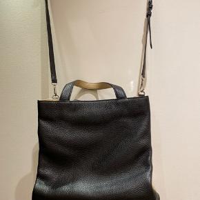 En noget anderledes lækker dobbelt taske i lækkert skind. Masser af rum og magnetlukning. Skulderrem kan tages af, så det er en håndtaske. Fremstår som ny. Sælges til under halv pris, så respekter venligst denne. Måler ca 30x30 cm.  Sælges med dustbag. Bytter ikke.