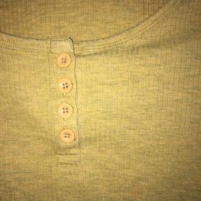 Kort top med en dejlig farve og lange ærmer med fire knapper ned ad brystet. Knapperne kan ikke knappes op. Toppen  går ikke over navlen. ☺️