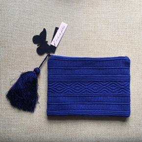 Stor unik clutch i blå struktur-strik med for af silke. Aldrig brugt og originalmærker sidder stadig på. Har lynlås, stor kvast (der kan tages af) og mindre lomme med lynlås indeni.  Nypris: 400 kr. Mål: 33 x 23 cm.  Kommer fra røg- og dyrefrit hjem. Kan sendes på købers regning.