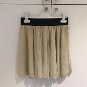 Super sød guld/glimmer nederdel med elastik i taljen og tyl. Brugt 1 gang.
