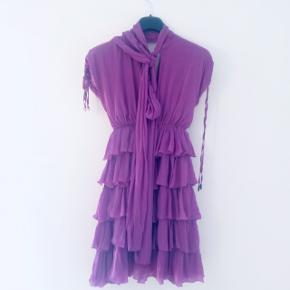 Smukkeste festkjole fra Just Cavalli i en Italiensk str 42 (svarer til 38). Brugt til bryllup, en dåb med en lille jakke, en sommerfest og en nytårsaften med strømpebukser/blazer. Silke-crepe, med supersmukt skørt og sløjfe/binde effekt i halsen, så den både kan være helt klædelig/dækket til, eller mere åbentstående. I en støvet syrenfarvet-lilla. Købt hos Karin Winther i Charl. Lund til 6999kr. BYD!
