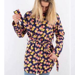 Fin lang skjorte med bælte fra Mads Nørgaard . Kun brugt sparsomt og i god stand uden huller, pletter, fnuller eller lign. Brystmål: 62 cm på tværs fra armhule til armhule, dvs 124 cm i omkreds. Længde: 89 cm fra nakken og ned. Søgeord: blomster blomstret skjorte shirt flower print mønster mønstret lang kimono gul blå orange bluse oversize løs