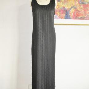 100 % NY: Flot sort lang kjole syet i smukt stof med et indvævet mønster  i sort i sort. Kjolen har 2 høje slidser på 50 cm.  Materialet er polyester  Brystvidde: 55 cm x 2 Livvidde: 52 cm x 2 Hoftevidde: 59 cm x 2 Længde: 139 cm  Ingen byt, og prisen er fast