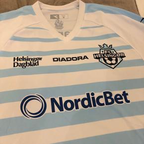 Sælger denne FC Helsingør hjemmebanetrøje fra sæson 2017/2018 i størrelse medium, da jeg ikke får den brugt. Den er brugt 1-2 gange, og er dermed i perfekt stand.  Kan afhentes i Hellerup eller sendes på købers regning med DAO.