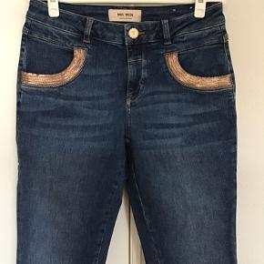 Sælger disse Mos Mosh jeans model Naomi Cube. Str. 27. Livvidde 37x2cm. Indvendig benlængde 77cm. Som nye, vasket 1 gang.  94% bomuld, 4% polyester, 2% elastan. Sender med DAO for købers regning.