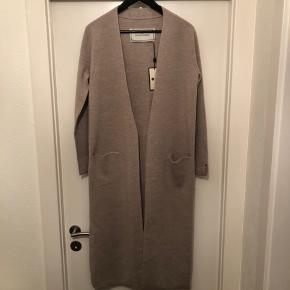 MB - lækker lang cardigan i Merino uld, kan både bruges med og uden bælte. Fine detaljer slids ved ærmerne og i siderne langs benet. Farven er beige/lys grå ish. str. S - Mp. 1400 kr Aldrig brugt - bytter ikke.