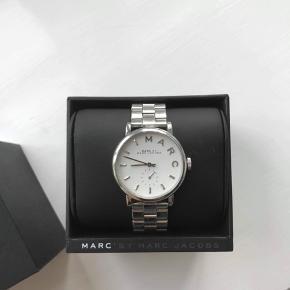 Flot sølv-ur fra Marc Jacobs i modellen Baker. Uret har ingen store ridser, men der er brugstegn i form af småskrammer. Der er tager nogle led af, men ledende haves stadig og kan sagtens sættes på igen. 😊