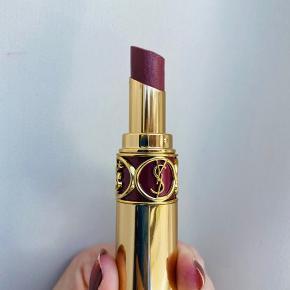 Rouge Volupté Shine Oil-In-Stick Lipstick fra Yves Saint Laurent er en plejende læbestift, der indeholder 60% koncentrater af sesoriske olier, der til sammen skaber en unik signatur af glans, enkelhed og skinnende farve til læberne. Læbestiften er langtidsholdbar.   Brugt meget få gange. Har et enkelt hak på toppen.