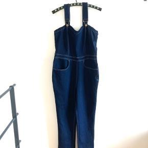 Str M/UK12. Overalls/smækbukser i 1950'er stilen med sweetheart udskæring og hjerter på baglommerne. Mørk jeans stof. I virkelig flot stand. Ingen pletter eller skader. Jeg har lagt buksebene op så de måler nu 75 cm.
