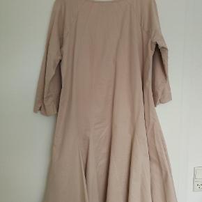 Rigtig fin kjole i pudderfarvet blødt stof. Skåret i baner, der skråner let udad. 3/4 lange ærmer, lommer.  Længde: 100 cm Brystvidde: 50 cm x 2 47 % bomuld, 43% polyester, 10% polyamid