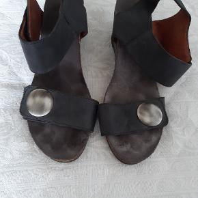 Lækre sorte Cashott sandaler med kilehæl. Sandalerne er fremstillet i kombination af læder og ruskind hvilket giver et rigtigt godt klima for fødderne.Sandalerne er også fremstillet med justerbare remme ved forfod og ankel for den bedste komfort. Kilehælen måler 6 cm, men er meget behagelig at gå med både pga kilehælen samt den bløde gummisål. Sandalerne er brugt meget få gange, og fremstår som nærmest nye.