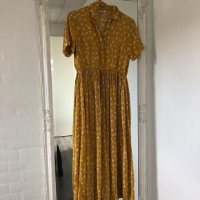 Lang kortærmet skjortekjole fra pieces i gul med blomster mønster sælges. Den er brugt et par gange sidste år, ellers hængt i skabet. Fejler intet