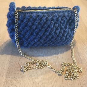 En håndhæklet taske fremstillet af ren Alpakka uld fra Sandnes Garn. Den er udført i en smuk boble-hækling med lynlås-lukning, og er beklædt med hvid bomuld indvendigt, som er slidstærk. Kæden er let, lavet af aluminium.  Farve: Petroleum  Str: 22x15 cm