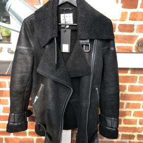 Smuk ubrugt bikerjakke / aviator jakke. Lavet af shearling gedeskind. Obs en lille læderstrop er faldet af og derfor den lave pris