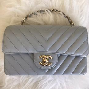 Pristine and never used 20S light grey caviar mini rectangle Chanel classic flap. Smooth and shiny lambskin. Chevron quilting. Light gold hardware. Made in France. Comes with full set including copy of original invoice. I also have the matching card holder (see listings). Gorgeous piece for those who missed out on this color. Selling at current retail price DKK 27'380.