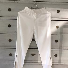 Virkelig cool og lækre hvide bukser fra Birgitte Herskind. Løs lidt joggingbuks model med gennemsigtig stribe hele vejen ned på begge sider. Lånlås ved anklerne. Kan ikke finde vaske- og størrelsesmærket, men de er små i str (i elastikken). Tror det er viscose.  Brugt en gang. Perfekt stand. Se mine andre annoncer!