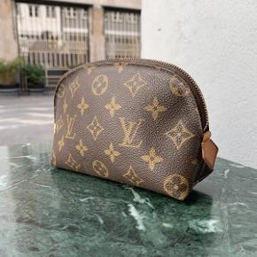 Ældre Pochette Kosmetiktaske fra Louis Vuitton af monogram kanvas.  Tasken fremstår i brugt stand med brugsspor.  Der medfølger ikke originalt købstilbehør til tasken.  Tasken måler ca 19x12cm.