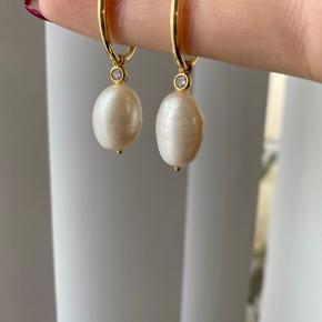Taget fra hjemme siden:  simpel creol med et smukt vedhæng bestående af en funklende zirkonia sten og en smuk naturlig baroque perle. (Da baroque perlen i smykket her er et naturprodukt, kan denne variere fra produkt til produkt og ligner muligvis ikke den på billedet i forhold til form.) Creolerne inkl. vedhæng måler 40 x 12 mm. De er brugt en gang men bryder mig ikke om at havde dem på Forgyldt Sterling sølv