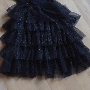 Fin mørkeblå kjole i tyl fra Name It med guld prikker. Kjolen er i mange lag, men stadig let og luftig at have på. Str 86, lidt lille i str.  NSN - Ingen pletter, huller, misfarvninger eller fnuller. Aldrig været i tørretumbler. Fra røg- og dyrefrit hjem. Prisen er plus evt porto, sender med dao, gls eller post nord. Eller afhentning i Varde.