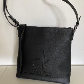 Calvin Klein taske sælges, har aldrig været brugt, er 27 høj, 24 bred og 6 dyb og så kan remmen gøres længere, efter behov. Tasken er købt i en Calvin Klein butik, så det er ikke en kopi. Sælges for 375,-.  Hvis du er i nærheden er du velkommen til at komme at se og prøve.