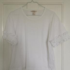 Fin hvid tshirt fra h&m med flæse på ærmerne. Trod brug er den stadig pæn hvis i farven og uden pletter osv.  Køber betaler fragt.