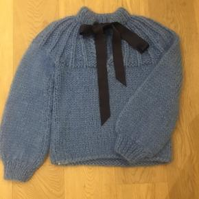 Sweater from Ganni with the bow detail in the back in colour marina.