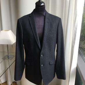 Smukt blazer i uld tweed fra Tiger of Sweden. Små ternet i sort og mørkegrå. Str. 48. Kun brugt få gange ved to festlige lejligheder. Står som ny og med ekstra knapper.